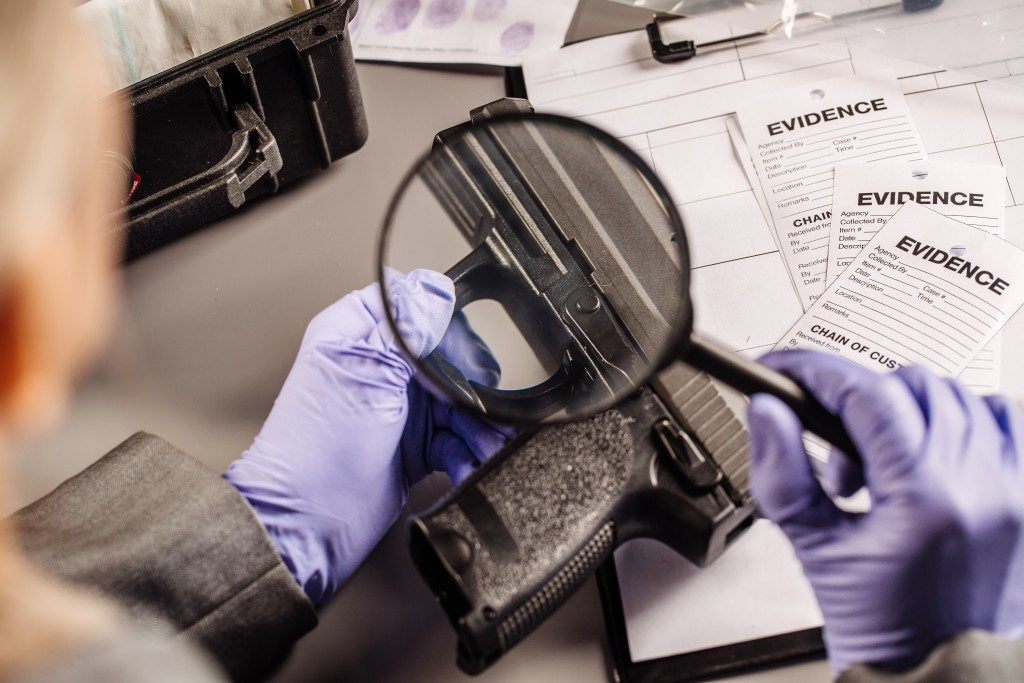 an investigator looking for evidence in the gun using a microscope