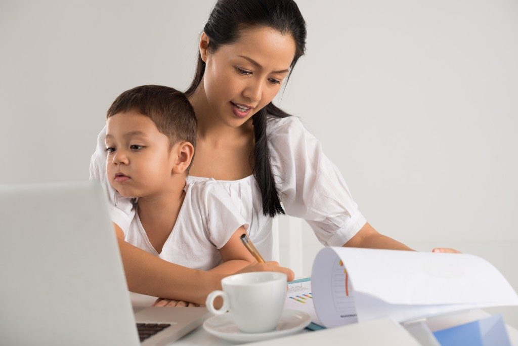 mom doing office work with her son on her lap