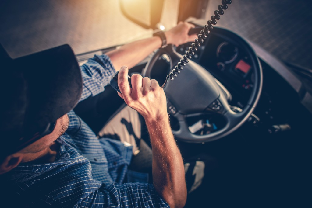 Man behid the truck's stearing wheel using the radio