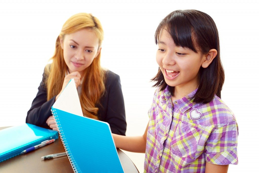 Girl studying English with teacher