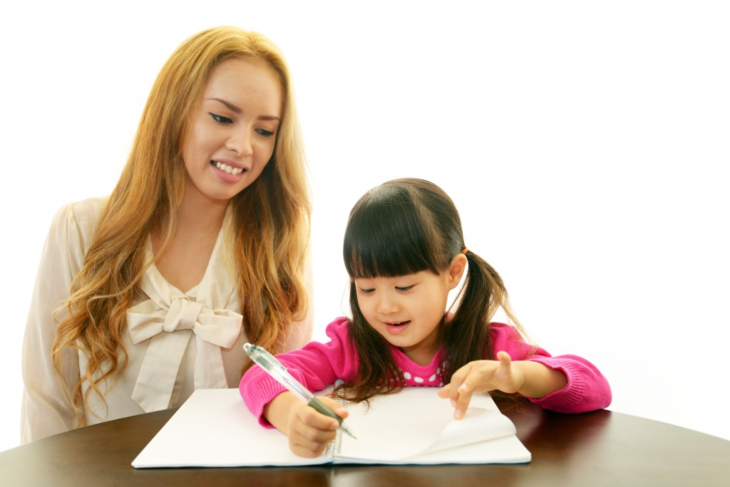 Little girl studying English with her teacher