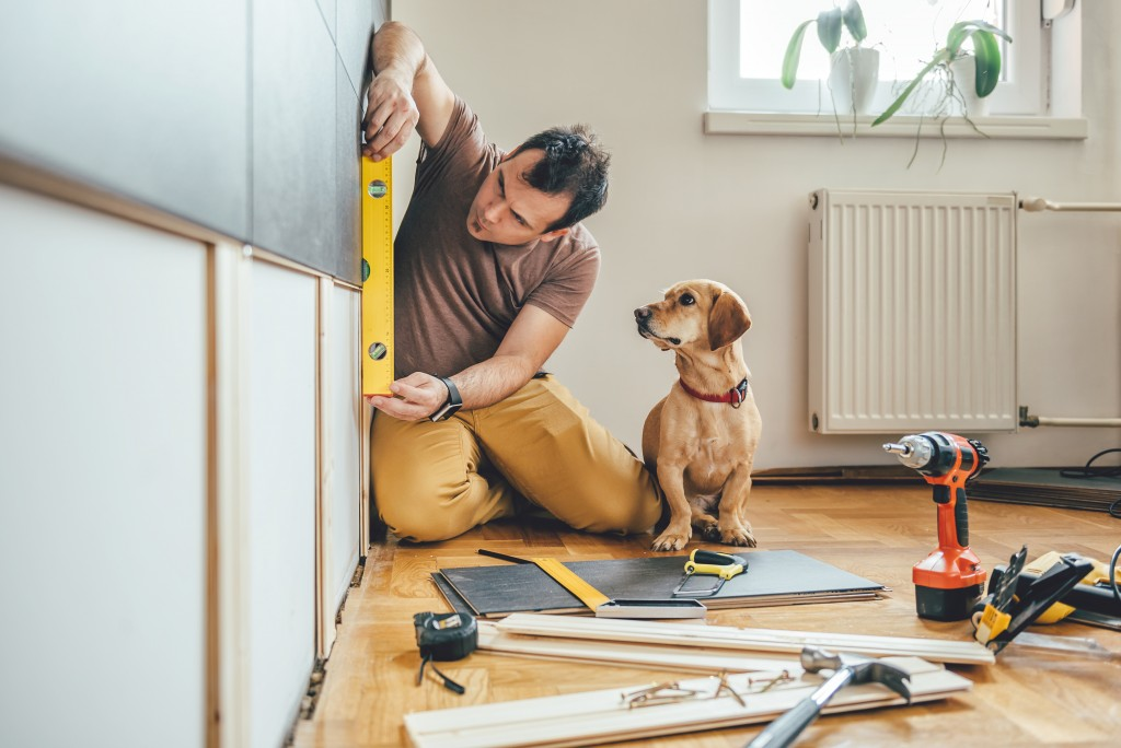 man fixing the house with his dog