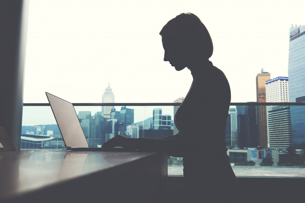 silhouette of woman typing with city background