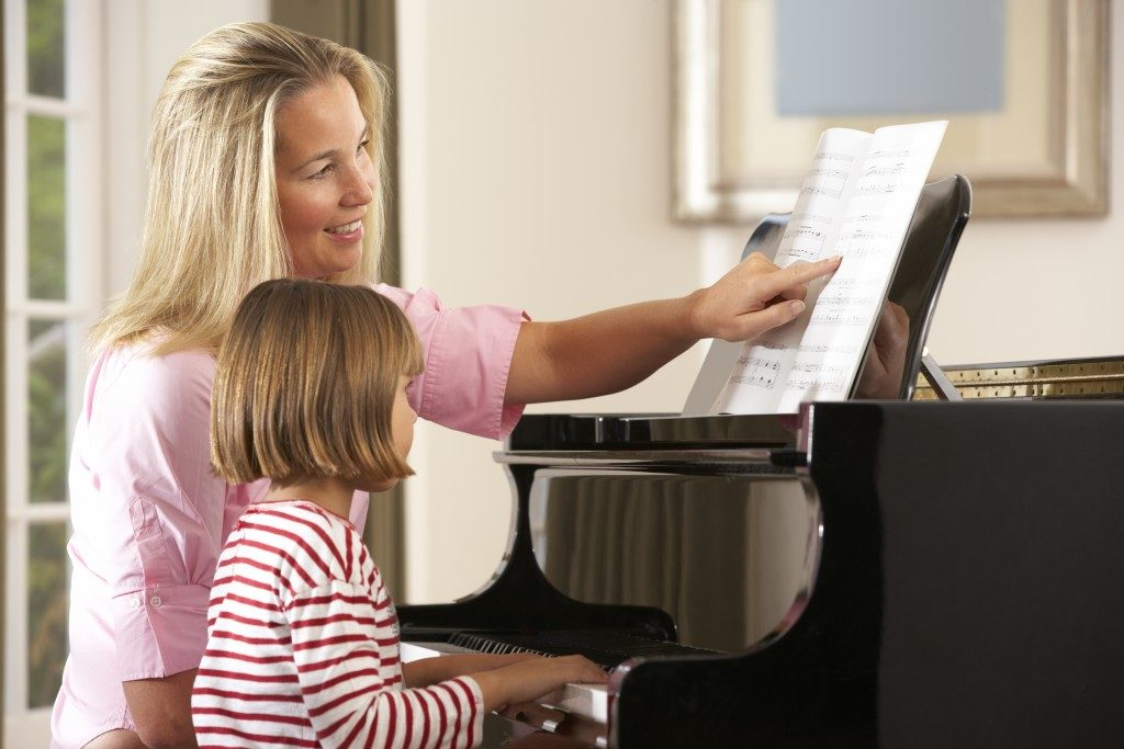 Young girl with piano teacher