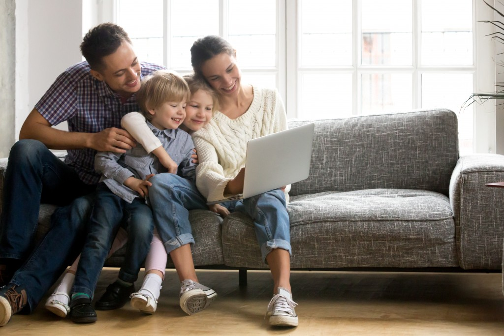 family of three watching on laptop