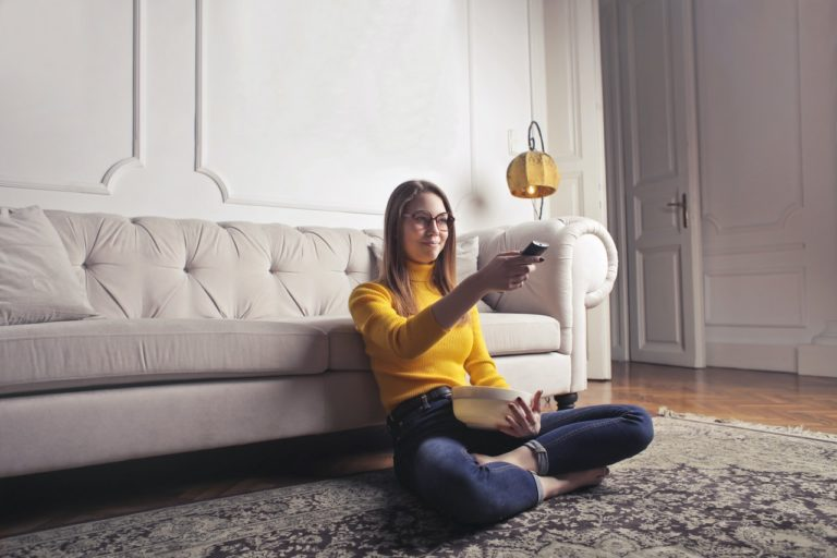 woman sitting on the floor watching tv holding a bowl of popcorn